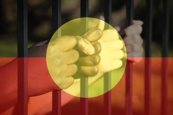Aboriginal child's hands on jail barred overlaid with Aboriginal flag.