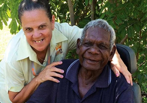 Aboriginal care worker with her arms on the shoulders of an elderly Aboriginal man in a wheelchair.