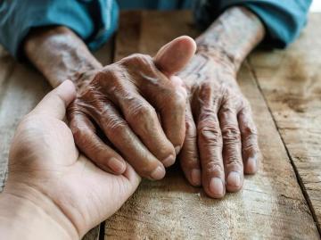 Elders hands in carer's hand
