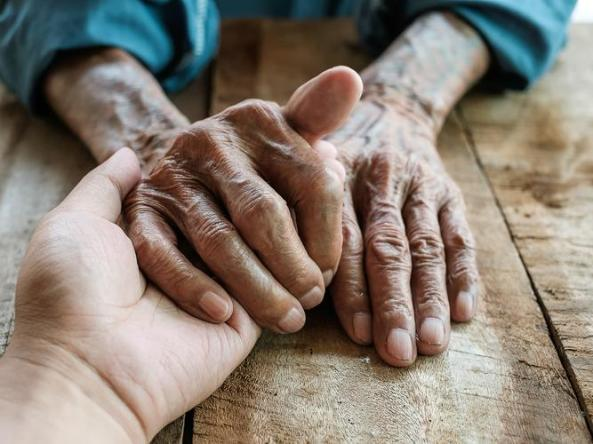 Elders hands in carer's hand