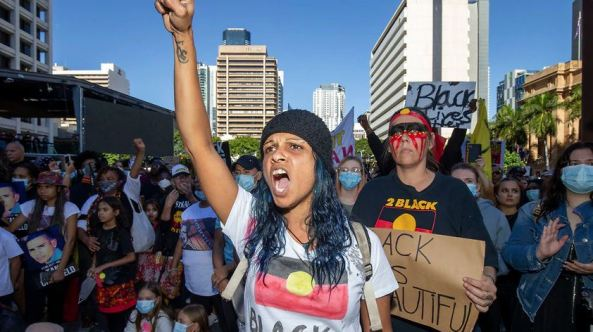 Black Lives Matter protest in Brisbane - photo of the crowd, Aboriginal woman fist in air, Aboriginal flag on white t-shirt