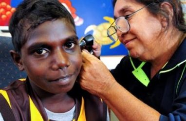 Health professional checking ear of Aboriginal boy