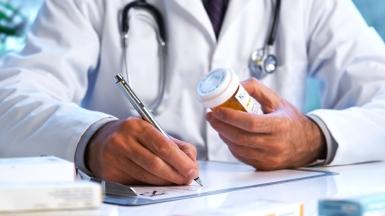 doctor's hands writing a prescription