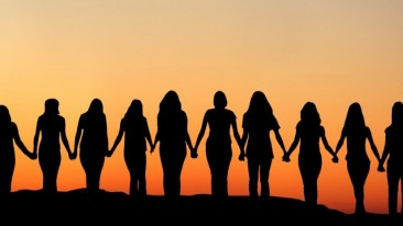 silhouette of 10 women holding hands at sunset
