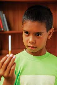 Aboriginal child holding & looking atan unlit cigarette