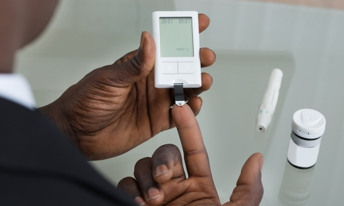Aboriginal person doing diabetes test pricking finger