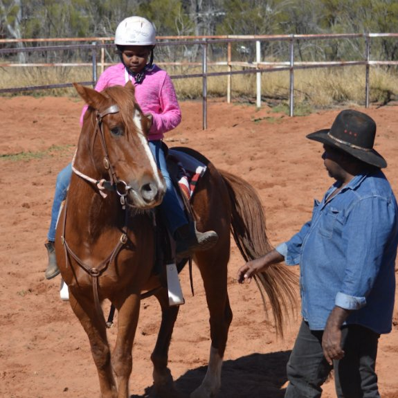young Aboriginal girl on horse & Aboriginal man trainer