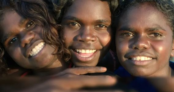 close up photo of three Aboriginal children smiling