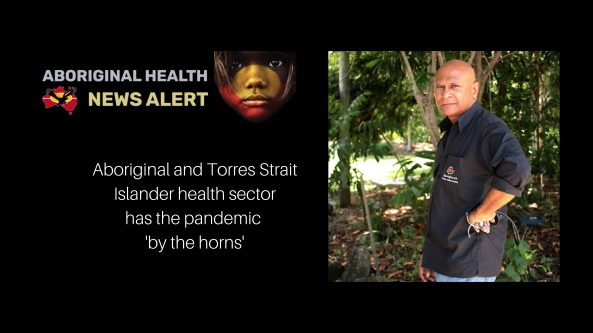 Dr Mark Wenitong standing new tropical foliage in Apunipima Cape York Health Council shirt