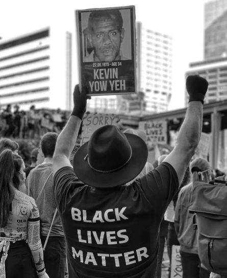back of BLM protester holding sign of face of Kevin Yow Yeh who dies in custody at 34 years