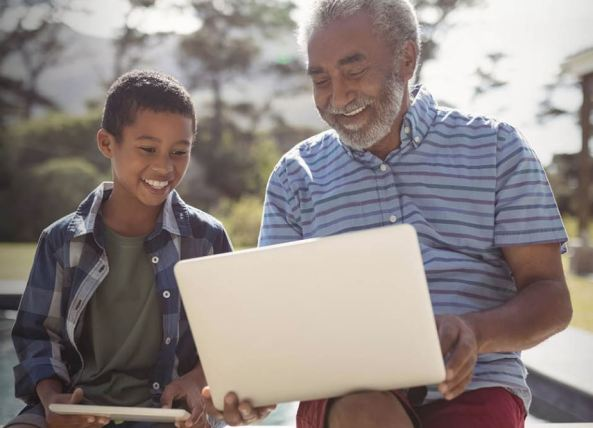 Aboriginal man & Aboriginal child looking at laptop