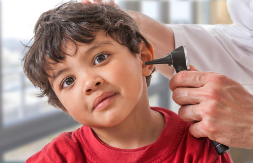 young Aboriginal child having his ear checked by health professional