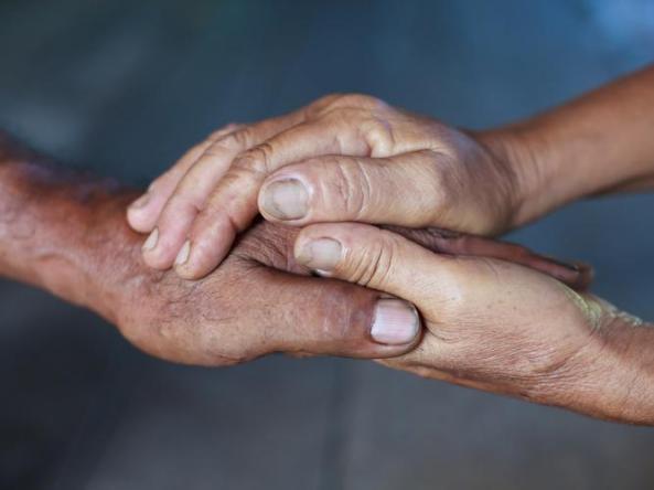 Aboriginal hand held within two other Aboriginal hands