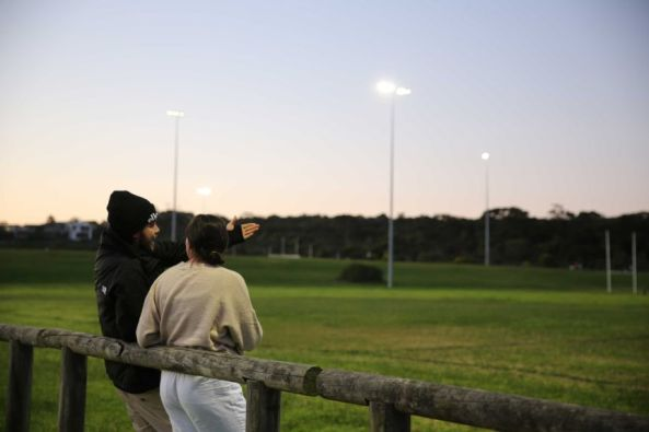 backs of Aboriginal Trei and Karlie Stewart leaning against would post rail fence looking at football field