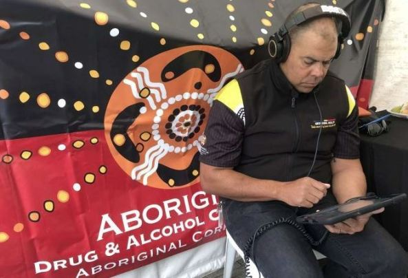 Aboriginal health professional sitting in from of Aboriginal D&A banner