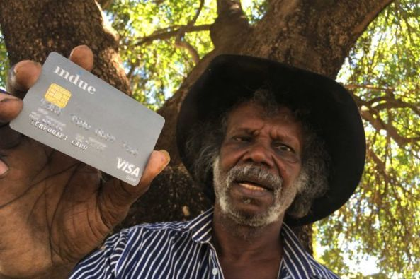 Aboriginal man under tree holding Cashless Debit Card to camera