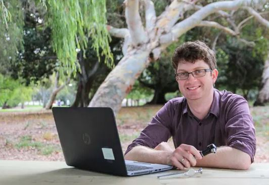 Dr Chris Brennan-Jones sitting outside with laptop