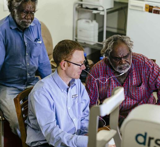 two Aboriginal men and health professional looking at monitor