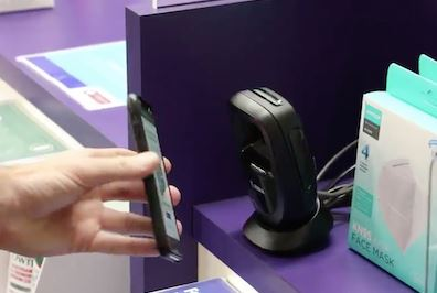 image of hand with phone held to scanning machine