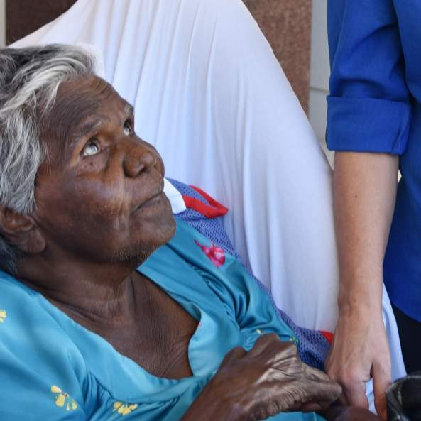 elderly Aboriginal woman in hospital bed looking up to nurse