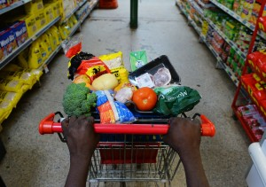 hands of Aboriginal person pushing trolley or health foods in outback store