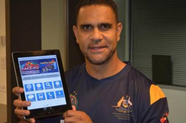 "AFL Indigenous All Stars coach Michael O'Loughlin with the ""Aboriginal Health in Aboriginal Hands"" app"