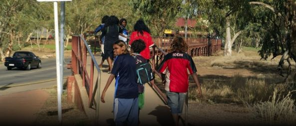 6 Aboriginal children walking across a foot bridge in rural Australia