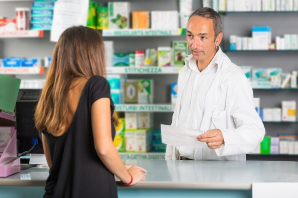 Pharmacist talking over counter to customer