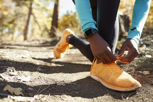 image of arms of Aboriginal person in running gear bending to tie shoelaces along bush trail