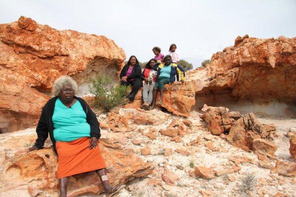 Five Aboriginal women, two Aboriginal children & a terrier dog sitting on bare weathered red rocks