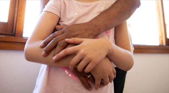 Aboriginal arms around child - torsos only set against wooden framed windows