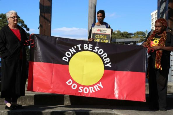 Aboriginal women holding Aboriginal flag with words 'Don't be Sorry, Do Sorry'