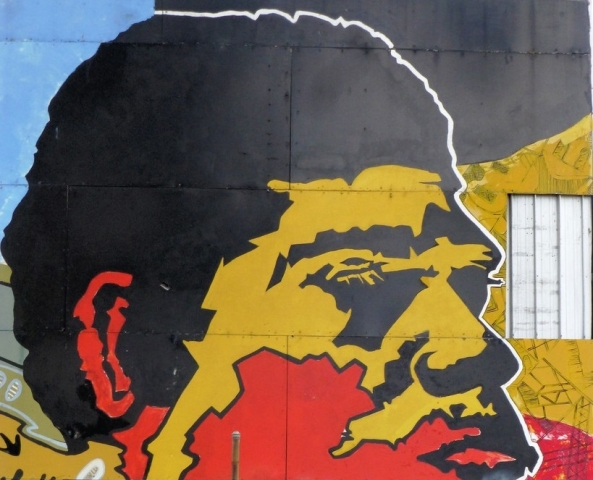 graffiti of Aboriginal man's face in red, yellow & black