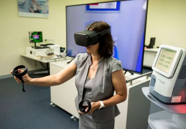 Werfen Australian NZ GM Sally Hickman demonstrates virtual reality blood testing - wears virtual reality goggles, hand is outstretched