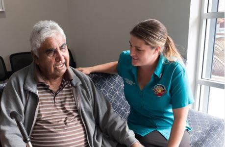 health worker with middle-aged Aboriginal man in home setting