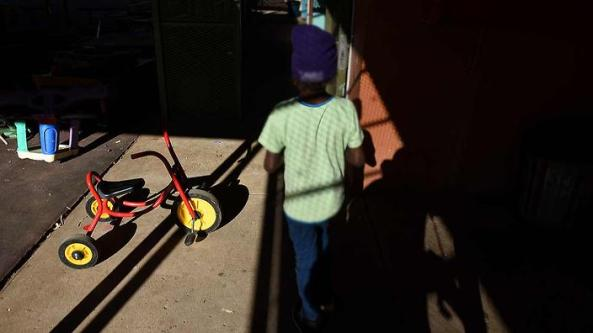young Aboriginal child in shadows outside with tricycle and parts of other play equipment visible