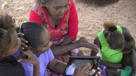3 Aboriginal women and two Aboriginal children with iPad outdoors sand