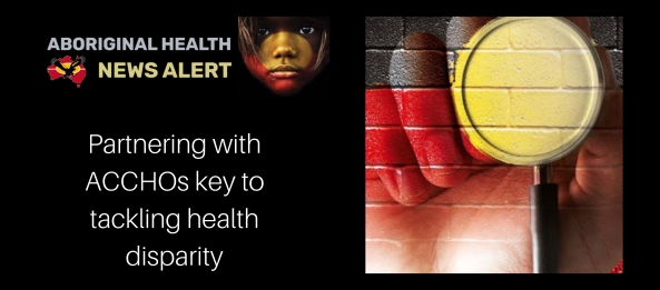 feature tile text 'partnering withACCHOs key to tackling health disparity', painting of brick wall with Aboriginal flag overlaid with hand holding stethoscope for yellow centre of flag