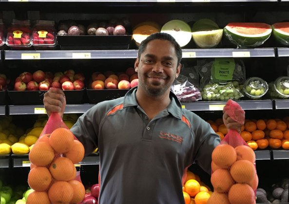 Aboriginal man in front of fruit in store holding bags of oranges