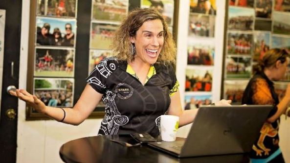 photo of Laura Thompson sitting in front of laptop at desk huge smile, arms outstretched