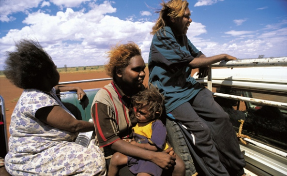 three Aboriginal women, one holding a young child in the back of a ute in the outback