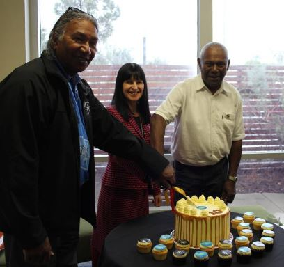 Elder, client and GP cutting 10 year anniversary cake