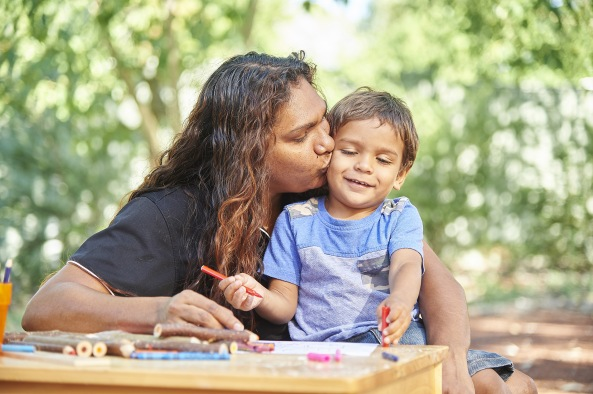 Aboriginal mum kissing small child on the cheek at table of activities in outside setting