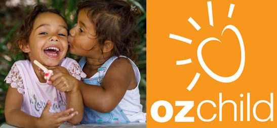 two Aboriginal young girls, one kissing the other on the cheek, OzChild logo