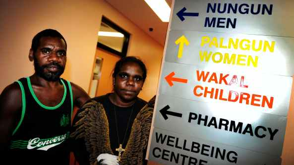 male and female Aboriginal people with pharmacy sign