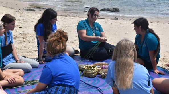 7 female students on rug on beach watching teacher give basket weaving demonstration