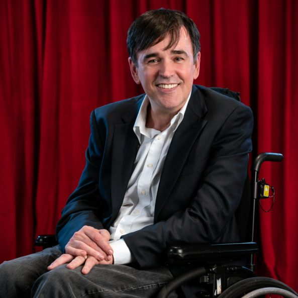 Australian comedian Tim Ferguson sitting in his wheelchair with red velvet stage curtain in the background