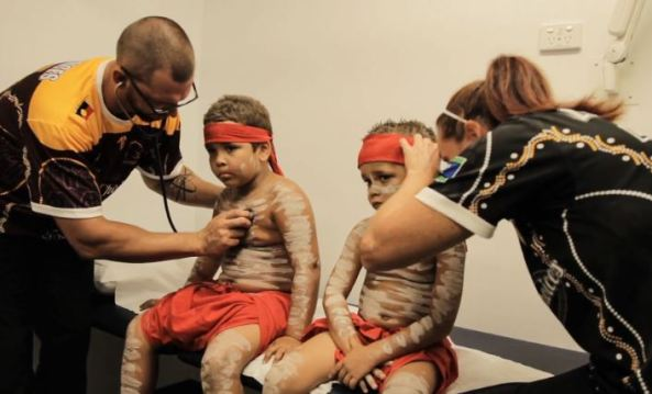 two small Aboriginal boys in traditional dress, one having heart checked & the other having his ear checked by health professionals