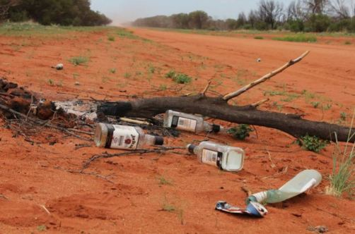 3 empty Jim Beam bottles, one squashed can etc on side of red dirt road