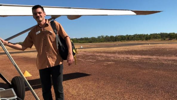 Aboriginal medical student holding the strut of a light plane on tarmac in outback